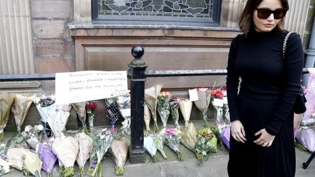 A woman views floral tributes left outside St Ann's Church, Manchester, following the Manchester Arena bomb attack.