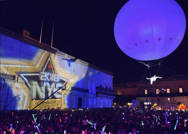 An acrobat floats over a crowd tied to a balloon in St Georges Square Valletta during the New Years Eve Celebrations on 31 December. Photo: Mark Zammit Cordina