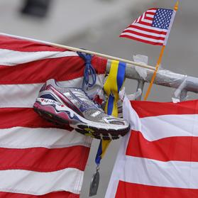 A running shoe with the date of the Boston Marathon bombings written on it, hangs beside a Boston Marathon medal and a small US flag at a makeshift memorial along Boylston Street in Boston, Massachusetts last Thursday. Photo: Reuters