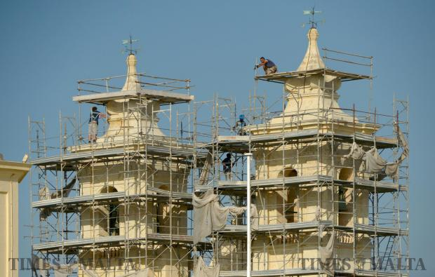 Workers remove the scaffolding around Gharghur Parish church on August 4 after renovation works were completed on the facade in time for the feast later on in the month. Photo: Matthew Mirabelli