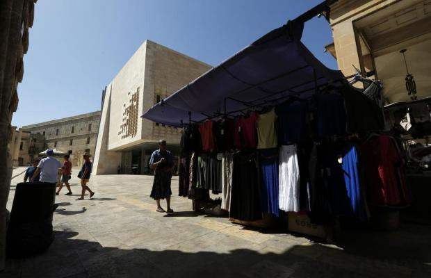 A hawker organises bargain clothing on his stall near Renzo Piano's landmark Parliament building in Valletta on August 1. Market stalls were set up across the street from the new Parliament building for the first time on Monday, a controversial move originally earmarked for 2015. Photo: Darrin Zammit Lupi
