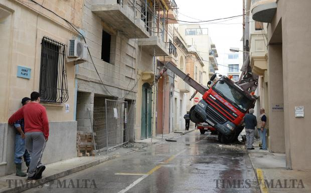 A concrete pumping vehicle lies on its side after tipping over in a street in Sliema on February 3. Photo: Matthew Mirabelli