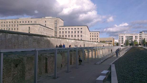 Bleak buildings behind what is left of the wall.