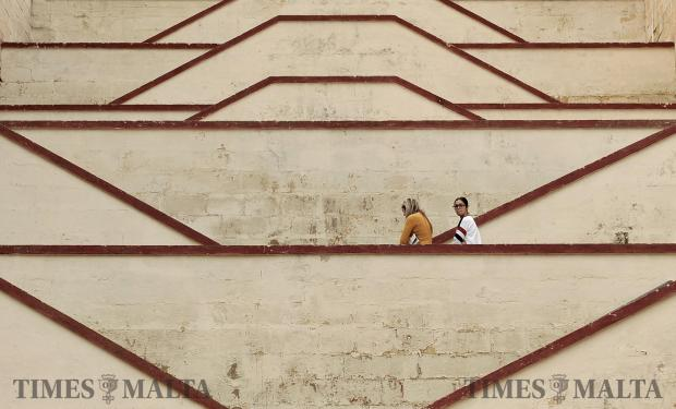 Two girls walk up a stair case in Cospiqua on February 8. Photo: Chris Sant Fournier