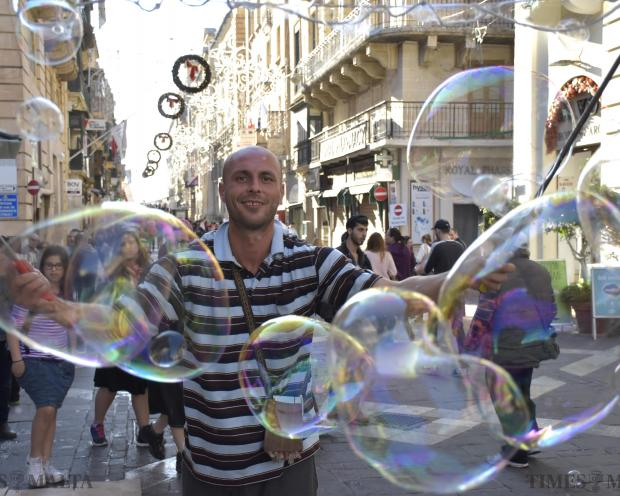 A busker blows big bubbles in Republic Street Valletta on December 9 drawing passers by. Photo: Mark Zammit Cordina.