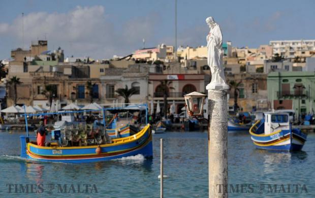 A fishing Luzzu passes by a statue of Jesus as it makes it's way to the Marsaxlokk quay on January 4. Photo: Chris Sant Fournier