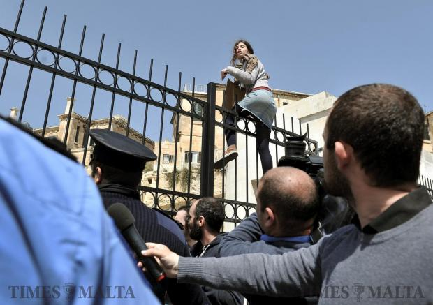 An activist climbs over a fence in protest against the transfer of a Sliema fuel station onto Luqa ODZ land on April 5. Photo: Chris Sant Fournier