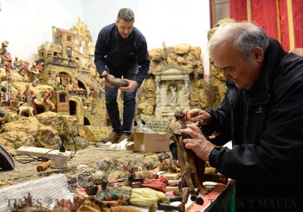 Fr Edgar makes some final touches to a figure before placing it in the traditional Neapolitan crib featuring a collection of 18th century crèche figurines on display at the Mdina Cathedral. on November 29. Photo: Matthew Mirabelli