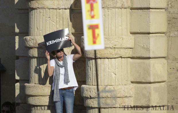 A woman uses a placard to protect her from the sun during an anti-corruption protest in Valletta on April 23. Photo: Mark Zammit Cordina