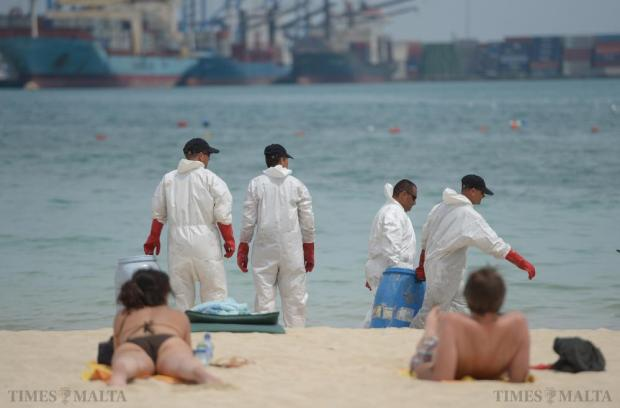 Members of Civil Protection attempt to remove oil from the water in Pretty Bay, Birżebbuġa after it was closed to bathers on June 12 due to a The spill was caused when a container was damaged by machinery in the Freeport, contaminated the water and sand. Photo: Matthew Mirabelli