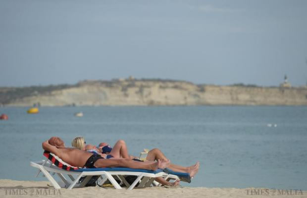 People make the most of the warm October sun at Pretty Bay, Birzebugia on October 20. Photo: Matthew Mirabelli
