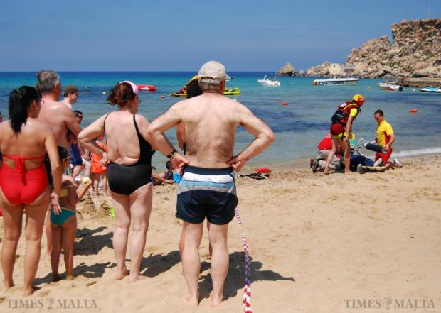 Bathers watch a Red Cross life saving team perform a demonstration of CPR on a dummy at Golden Bay in Ghajn Tuffieha on June 30. Photo: Mark Zammit Cordina