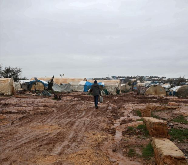 A man walks in the mud near makeshift shelters following heavy rains, at a camp for displaced people in the village of Atme, in Syria's mostly rebel-held northern Idlib province.