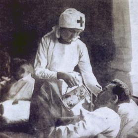 A Red Cross nurse tending the wounded.