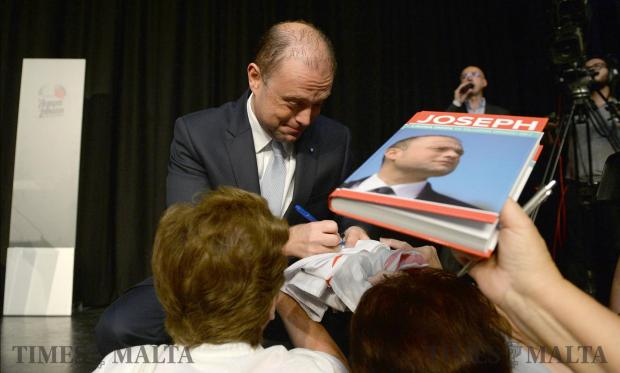Prime Minister Joseph Muscat signs books at a senior citizens rally at the City Theatre in Valletta on May 29. Photo: Matthew Mirabelli