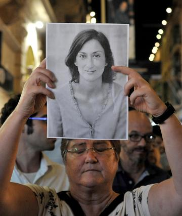 A woman holds up a portrait of Ms Caruana Galizia at a vigil marking one year since her assassination. Photo: Chris Sant Fournier