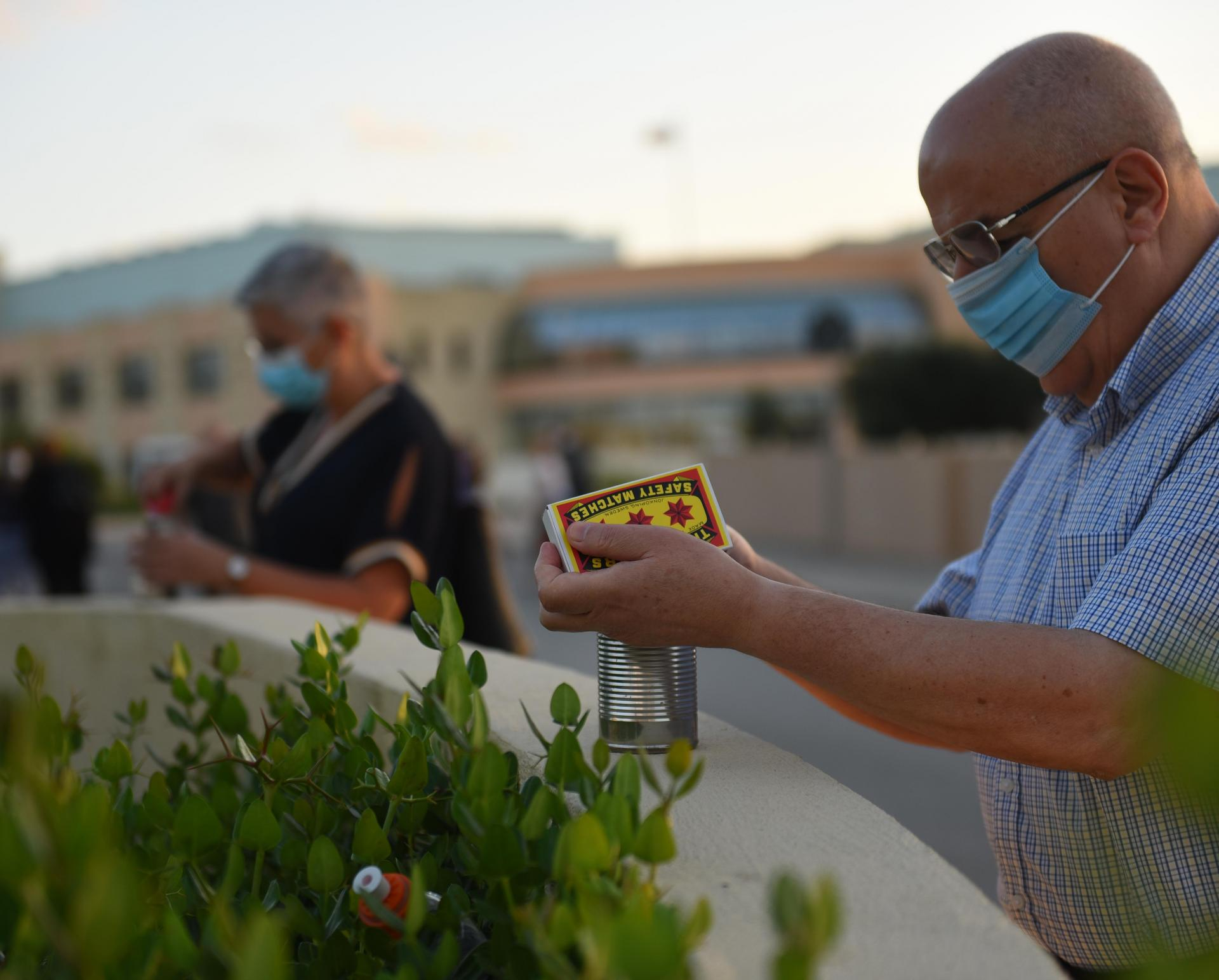 Relatives of COVID-19 victims light candles outside Mater Dei Hospital to honour their loved ones. Photo: Chris Sant Fournier