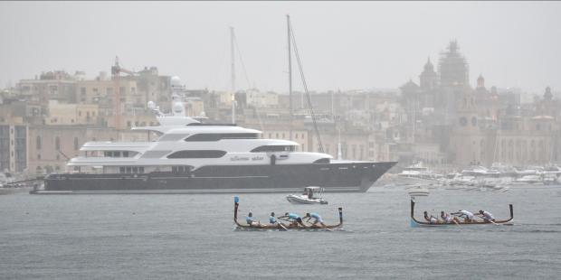 Rowers struggle under heavy rain during the Victory day regatta races against the backdrop of a Super yacht held in the Grand Harbour on September 08. Photo: Mark Zammit Cordina