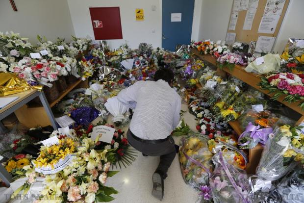 A member of the public lays flowers at the Mater Dei Hospital mortuary where the bodies of 24 migrants lie in Tal-Qroqq on April 22. Public outrage over the deaths peaked this week after up to 800 migrants died last Sunday when their boat sank on its way to Europe from Libya. Photo: Darrin Zammit Lupi