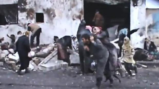A video image taken from a Shaam News Network video, which has been authenticated based on its contents and other AP reporting, shows a Syrian man carrying an elderly woman after a government airstrike hit the Hama Suburb of Halfaya, Syria.