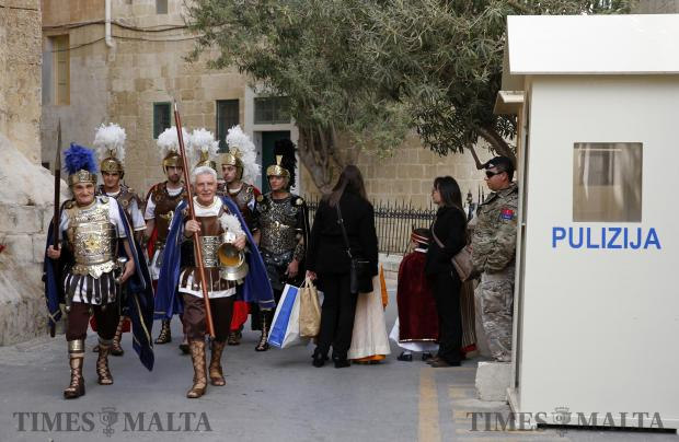 Men dressed as Roman soldiers walk past a sentry box outside the French diplomatic residence while waiting to take part in a Good Friday procession in Zebbug on March 25. Photo: Darrin Zammit Lupi