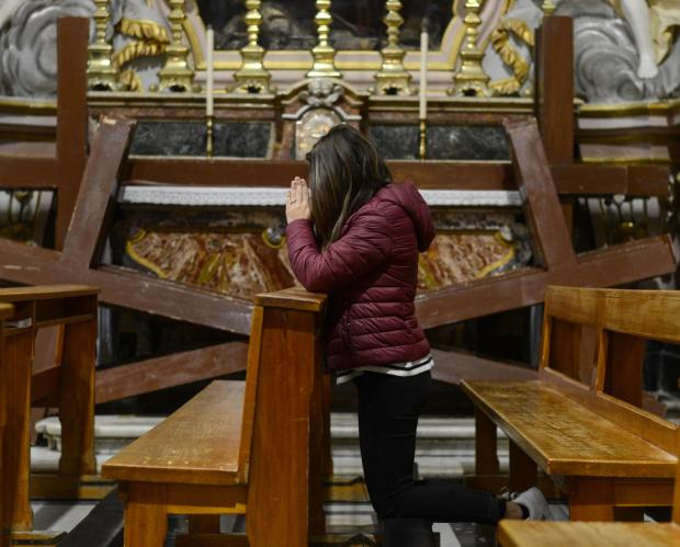 A woman prays at the St Philip of Agira, church in Żebbuġ on March 26 Photo: Jonathan Borg