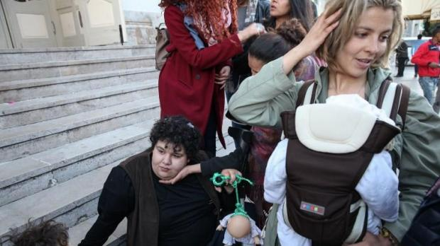 A protester holds a baby doll while a mother is holding her baby during a demonstration held on Avenue Habib Bourguiba in Tunis.