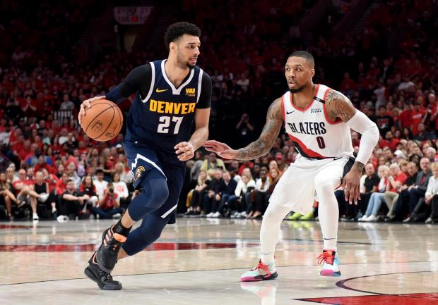 Jamal Murray (left) of the Denver Nuggets drives to the basket on Damian Lillard of the Portland Trail Blazers.