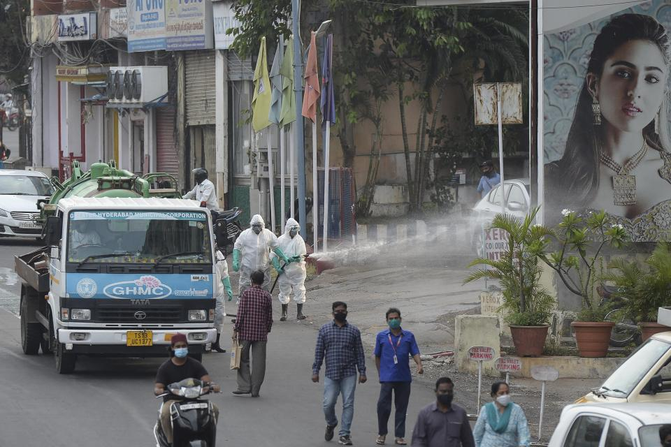 Members from the Disaster Response Force (DRF) of Telangana State, wearing protective gear spray disinfectant on a street against the spread of the Covid-19 coronavirus in Hyderabad.