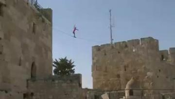 Slackliner walks between towers in Jerusalem