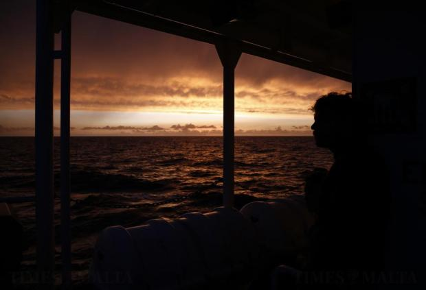 A crew member on the Migrant Offshore Aid Station (MOAS) ship Topaz Responder watches the sunset as the ship stands-by for migrants in distress in international waters off the coast of Libya on June 21. Photo: Darrin Zammit Lupi