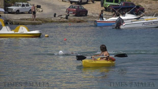 A girl on a canoe looks back to see a competitor arriving at Marfa after competing in the annual Malta-Gozo-Malta and Gozo-Malta swim on August 27. Photo: Mark Zammit Cordina