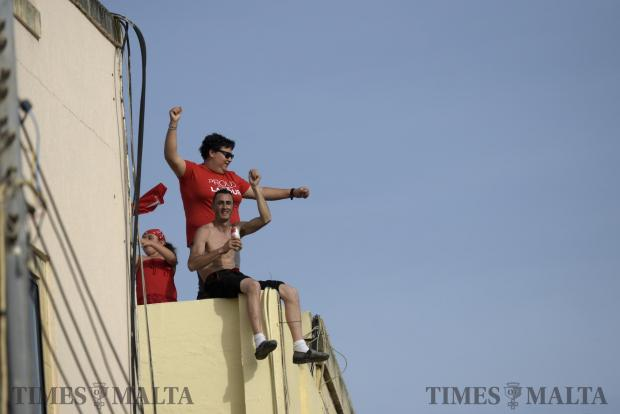 A man sitting on the edge of a rooftop with a can of beer in his hands waves during a meeting held by the Labour party in Zabbar on May 7. Photo: Mark Zammit Cordina