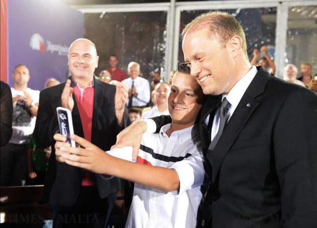 Prime Minister Joseph Muscat stops for a photo with a boy at an activity in Senglea on May 17. Photo: Matthew Mirabelli