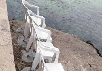 'Oh my Malta'... plastic chairs cemented to the quay