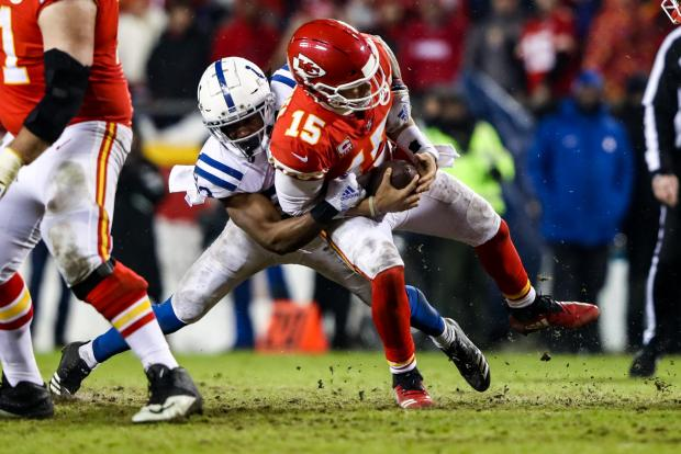 Patrick Mahomes #15 of the Kansas City Chiefs is hit by Kenny Moore #23 of the Indianapolis Colts.