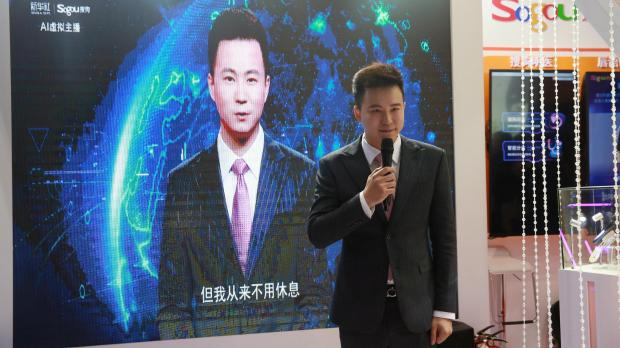 Xinhua news anchor Qiu Hao stands next to an AI virtual news anchor based on him.