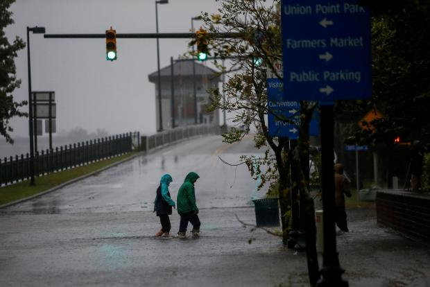 People walk on a local street as water from Neuse River starts flooding houses upon Hurricane Florence.