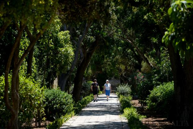 A couple enjoys the shelter from the sun whilst strolling around the gardens of San Anton in Attard on June 12. Photo: Matthew Mirabelli