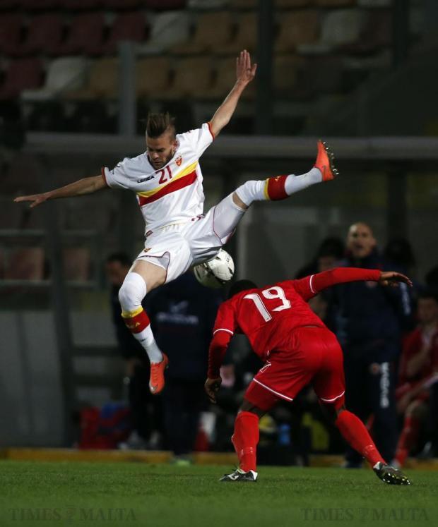 Montenegro's Veljko Batrovic (top) jumps over Malta's Joseph Mbong during their Under-21 football match at the Hibs Stadium in Corradino on March 23. Photo: Darrin Zammit Lupi