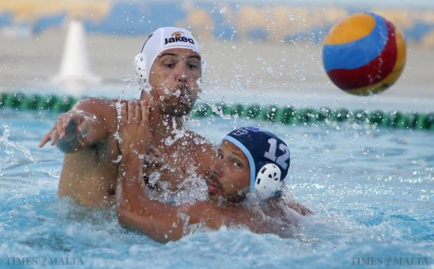 Neptunes' Steve Camilleri (left) slips the ball past Sliema's Nikola Dedovic during their waterpolo National League match at the National Pool in Tal-Qroqq on July 12. Photo: Darrin Zammit Lupi