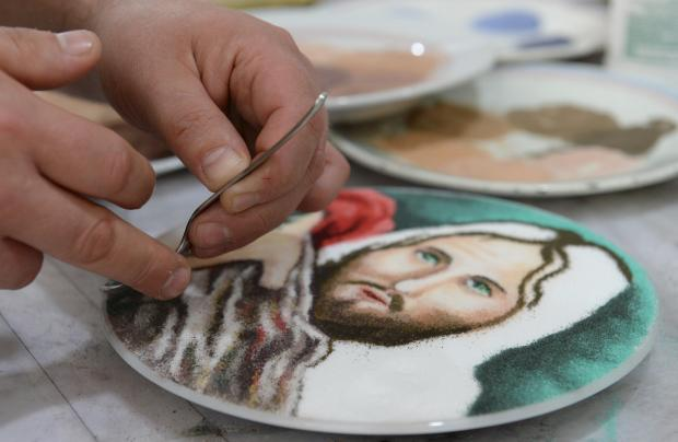 A member of the Domus Pius IX Society carefully sprinkles grains of coloured salt onto a design at their premises in Cospicua on March 31. Photo: Matthew Mirabelli