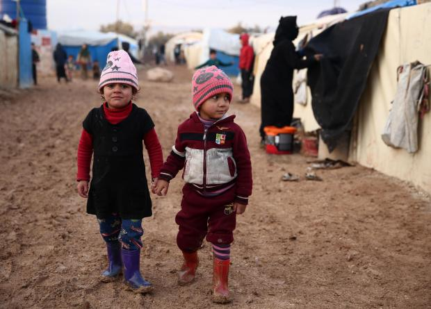 Syrian children walk together in the mud past tents at a camp for the displaced near the village of Shamarin, near the border with Turkey in the northern Aleppo province. Photo: AFP
