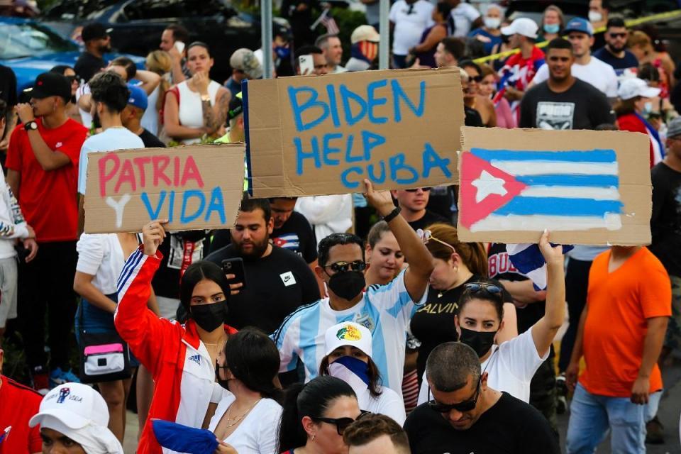 """La gente se manifiesta, algunos con pancartas que dicen """"Patria y Vida"""" y con la bandera nacional cubana, durante una protesta contra el gobierno cubano en Miami."""