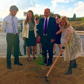 French Ambassador Béatrice le Fraper du Hellen planting a tree in Żebbuġ watched by Environment Minister José Herrera.