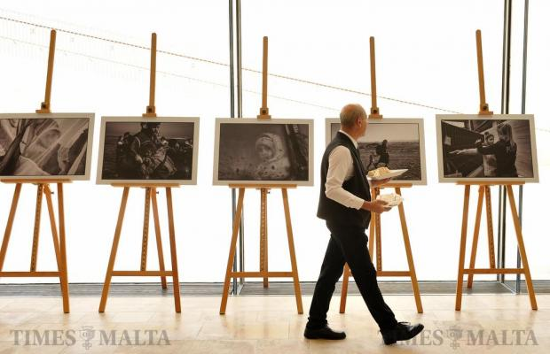 A waiter looks at photographs at the opening of the European Parliament exhibition paying tribute to female refugees at the Malta Parliament on March 6. Photo: Chris Sant Fournier