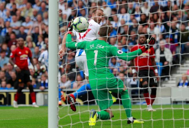 Glenn Murray flicks the ball past Man. United goalkeeper David De Gea.