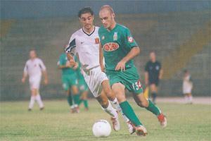 Floriana defender Ian Azzopardi moves past Gilbert Agius