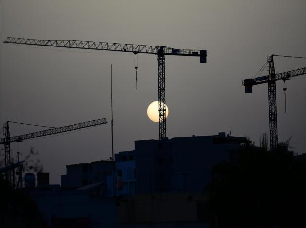 The dusty atmosphere makes the sun resemble the moon as it sets on three tower cranes in Santa Venera on July 25. Photo : Jonathan Borg