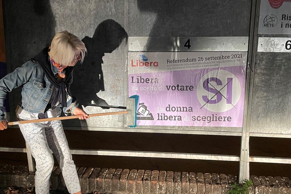 Pro-abortion campaigner, and doctor, Francesca Nicolini puts up posters on the night of September 9, 2021 at the start of the campaign for the upcoming September 26 referendum on the legalisation of abortion in San Marino..